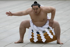 Mongolian-born grand sumo champion Yokozuna Asashoryu wears a ceremonial belly band as he performs a ring-entering ritual at Meiji Shrine in Tokyo January 7, 2008. Asashoryu was banned in August 2007 and fled to his homeland after he outraged fans when he was caught on video playing soccer while supposedly out of action with a back injury. REUTERS/Toru Hanai (JAPAN) - RTX5ATL